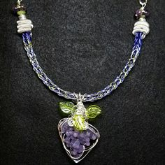 3 tone lavender,  peridot,  and silver viking knit necklace with silver spiral end caps, peridot and amethyst beads and a silver wire wrapped grape agate (otherwise known as Purple Botryoidal Chalcedony) and green glass leaf beads.