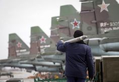 A serviceman carries a air-to-ground missile next to Sukhoi Su-25 jet fighters during a drill at the Russian southern Stavropol region, March 12, 2015. Russia has started military exercises in the country's south, as well as in Georgia's breakaway regions of South Ossetia and Abkhazia and in Crimea, annexed from Ukraine last year, news agency RIA reported on Thursday, citing Russia's Defence Ministry. REUTERS/Eduard Korniyenko (RUSSIA - Tags: POLITICS CIVIL UNREST MILITARY)