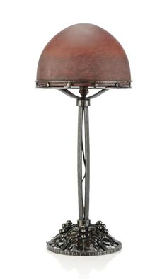 AN ART DECO WROUGHT-IRON TABLE LAMP WITH GLASS SHADE BY DELATTE -  CIRCA 1930