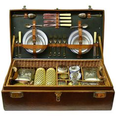 An unusual leather cased hamper that has a metal lining and lift-out wicker tray. This six person hamper comprises plated drinks beakers, plated cutlery, plated food tins, copper kettle or teapot, wicker covered glass flasks and enamel plates and cups, circa 1925.