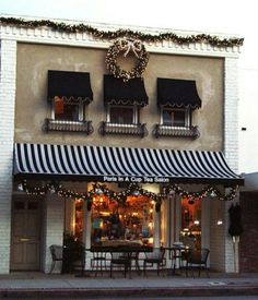 Store front with striped awning - Tea Shop. dressed for Love the lighted wreath and garland on top!