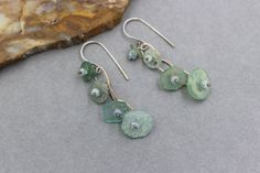 SALE! To celebrate the New Year, use coupon code: HAPPY2017 to save 17% off everything in the shop for the month of January. New items added regularly.  These earrings are long and have a very Bohemian feel. The beads are made from pieces of Ancient Roman Glass found in Afghanistan. These beads have gorgeous pitting, patina and iridescence from being buried in the ground for a thousand years. The glass is in pale blue, aqua and green shades. I made a small fine silver chain to dangle the…