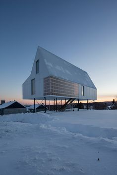 Stilts elevate this small winter cabin by Delordinaire above a snow-laden slope in Quebec, sheltering beneath its base an outdoor living space with a stove.