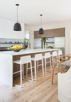 A kitchen with glossy white laminate cabinets, frosted-oak accents, and marble… Apartment Therapy, Layout Design, Design Ideas, Mirror Wall Tiles, Wood Counter Stools, Bar Stools, Kitchen Stools, Iron Console Table, White Kitchen Cabinets