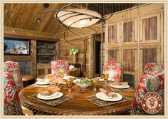 I am loving these colorful chairs in this barnwood dining room!