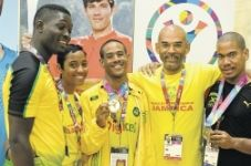 Coches Alecia Newman (second left) and Gabriel Heron (second right) join medal-winning swimmers (from left) Leon Barclay, Jonathan Lowe, and Nicholas Mcbean.