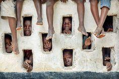 Timothy Allen. Children watching an Oxfam team at work, Grand Gedeh, Liberia
