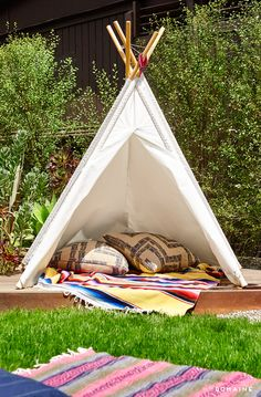 Teepee in backyard with pattered pillows