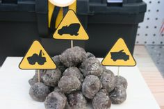 A pile of donut holes looks like rocks with Construction Signs cupcake toppers
