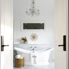 Exquisite master bathroom features a freestanding tub placed under a tub filler mounted on a ...
