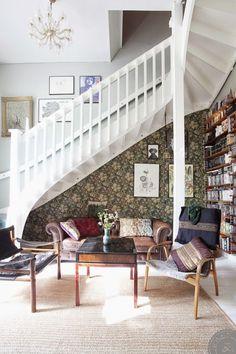 A sala de estar é um encanto, feita no espaço que fica embaixo da escada. Apesar de compacta, tem cantinho para tudo: as estantes ocupam quase toda a parede oposta à janela e emolduram o batente da porta. Nas prateleiras, uma infinidade de livros e coleções de discos de vinil de estimação.