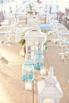 Long tables, burlap runners, white hydrangeas inside blue mason jars for centerpieces, alternating with white lanterns and votives filled with sand