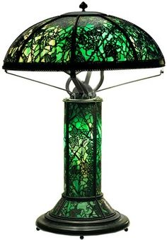 lighting, New York, Rivere art glass table lamp [Riviere Studios], American, New York, eight-paneled dome shade with green patinated finial, beading and border with metal grapevine decoration overlaying green slag glass, seated on a conformong four paneled green slag and grapevine decorated cylinder base flaring t 10', beaded and grauated base raised on four ball feet, lit with three sockets under shade ona one internal ligt in base. Circa 1895-1925