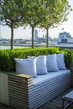 Rooftop in Bermondsey | Olive trees underplanted with rosemary surround contemporary built in bench | Charlotte Rowe Garden Design