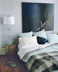 What a fabulous mix of almost a cabin feeling but the addition of the lamp and the Euro's in a matching colour add a whimsical feel to the room.
