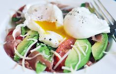 breakfast salad: avocado, tomato and parmesan, topped with a poached egg.  a cracked egg makes everything look so tasty.