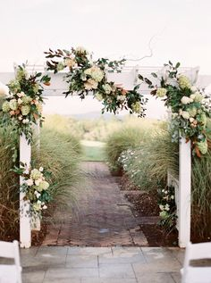 Elegant, outdoor wedding ceremony decor - white wedding arch with greenery garland and florals {Tourterelle Floral Design}