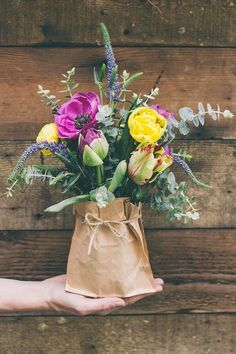 Mixed in season flowers in Mason jars and brown paper bags for center pieces. Mason jars can be reused for canning and paper bags can be recycled !