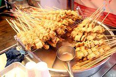 부산 오뎅 BUSAN ODENG (BUSAN'S FISH CAKES):Busan (2nd largest city in South Korea) is known for its amazing seafood, and Busan fish cakes are considered to be the best. A South Korean street food, the fish cakes are put on long skewers, and kept hot in a delicious, one-of-a-kind broth. Eat at the street food stand, grab a couple, dip in soy sauce, and enjoy. Count the sticks and pay after (only 1,000 won ~ 1,500 won each!