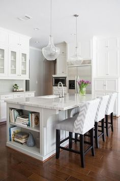White and gray kitchen features white cabinets paired with New Macabus White Quartzite countertops and a white and gray herringbone tile backsplash, Ann Sacks Savoy Herringbone Tiles.