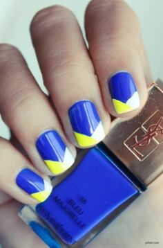 Dark blue nails with a yellow and white crossover design at the top