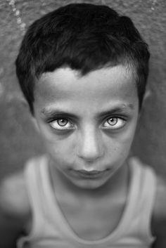 Niño palestino Ahmed Faium, de ocho años, mira al fotógrafo en el campo de refugiados de Jabaliya, en la Franja de Gaza (Ali Ali/EFE)