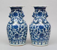 A pair of antique Chinese blue and white open baluster-shaped vases with scalloped rims, decorated with a pair of dragons on the front and back, scrolls of blue flowers and leafy tendrils, and foo dog-shaped handles, circa 1870.