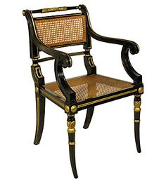A lacquer and gilt caned Regency style armchair based on the klismos chair.
