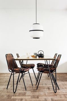 Minimalist dining space with a retro pendant light, leather dining chairs, and a retro table