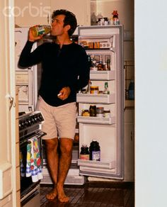 Singer Chris Isaak Drinking From a Bottle