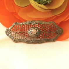 """Little old silver mesh brooch paste stone antique This beautiful little brooch is old! Set in the center is one clear glass paste stone. A thin perforated mesh of silver tone metal is attached to an ornate frame. Dating from about 1910s to 1920s, it shows its age with lots of patina and surface wear. (I personally love when antique jewelry looks old!) The old style C clasp pin back works well. This would make a wonderful """"something old"""" to wear on your wedding dress.  Inventory…"""