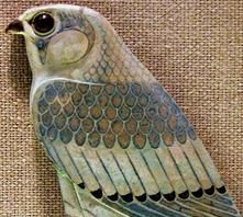 Photograph; Faience composite hieroglyph in the form of a falcon. Circa. Late Period to Ptolemaic Period, 4th Century B.C. Materials; faience paste, silica sand, glaze minerals and constituents.  Information; There has been some restoration of the artifact, the right claw foot is missing as well as some of the paint work. This composite hieroglyph was excavated at Hermopolis, El Ashmunein, Middle Egypt, Egypt.  COPYRIGHT ©