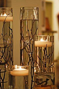 Assorted tall glass cylinder vases, filled with water, submerged twigs and branches, topped with floating candles