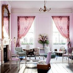 tall city street windows covered with mauve colored curtains.