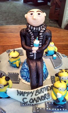 Despicable Me, Minion cake! All edible, buttercream with candy clay handmade decorations on a 10in round 2 layer cake! Gru is sitting on one of the birthday boy's cupcakes he stole, but then tried to make up for it by the mini cupcake he's holding! The background of the cake was inspired by Gru's Laboratory and the game Minion Rush. https://www.facebook.com/angelas.cakes2011