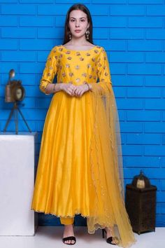 Exquisitely embroidered with traditional design, this yellow chanderi anarkali suit which will reflect the charm of high-end fashion. This round neck and 3/4th sleeve wedding wear dress accentuated with cutdana and sequins work. Accompanied by a matching cotton silk cigarette pants in yellow color with yellow net dupatta. Cigarette pants are plain. Dupatta embellished in sequins work. #anarkalisuit #usa #Indianwear #Indiandresses #andaazfashion