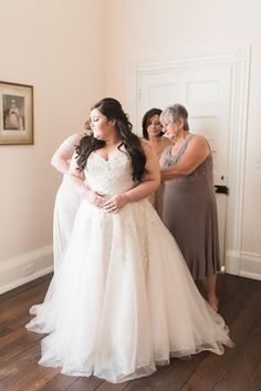 Mother, grandmother, and maid of honor getting the bride ready on her wedding day