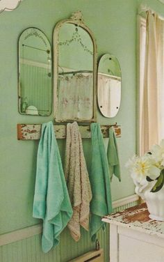 Beautiful grouping of vintage mirrors and salvaged board on sage green walls and beadboard