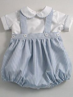 Oxford stripe baby romper suit. Two piece romper suit in English cotton Oxford. Peter pan collar top with short sleeves in white Oxford cotton, piped with the stripe to match the romper bottoms. Back buttons. The romper bottoms, made in blue/white striped Oxford cotton, generously gathered, have side openings, adjustable elastic in the back waist …: