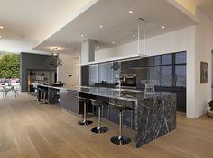 un îlot en marbre gris et des accents métalliques dans la cuisine spacieuse