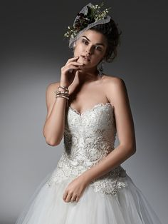 Sottero and Midgley - SIGOURNEY, Layers of lightweight tulle create the gorgeous skirt of this whimsical ball gown, featuring a lace and Swarovski crystal studded bodice. Finished with sweetheart neckline and pearl buttons over zipper closure.