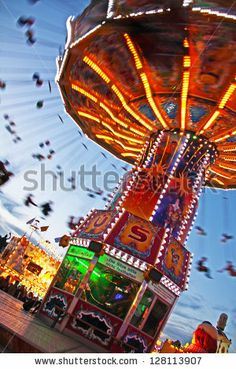 MUNICH - OCTOBER 4: An illuminated carousel is spinning at the Oktoberfest fair ground in Munich on the night of October 4, 2010 in Munich, Germany. - stock photo