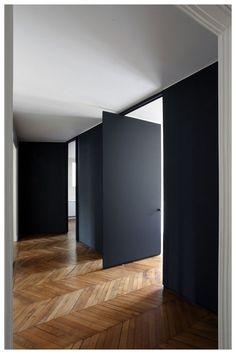 black pivot doors with herringbone wood floor