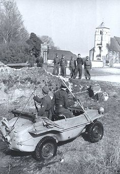 A group of soldiers have just driven out of a body of water and have raised the propeller mechanism as other soldiers wait to hear what they have found using a stick gauge for inspecting the depth