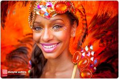 All smiles in her stunning red carnival outfit complete with feathers and jewels in Bacchanal, Jamaica.