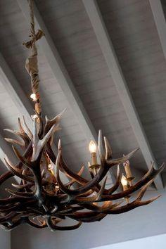 Le lustre Cervus Design en corne de cerf est une pièce forte du salon. - Mieux que le chalet, l'appartement esprit montagne - CôtéMaison.fr
