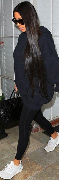 Who made  Kim Kardashian's black sunglasses, handbag, and white sneakers?