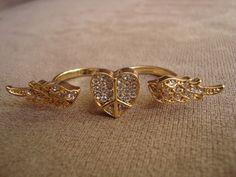 """Anel em metal dourado com o símbolo """"Paz e Amor"""" no formato de coração e asas. Aplicação de strass Swarovski branco.  Aros 17 (diâmetro: 1,72cm) e 18 (diâmetro: 1,75cm) R$45,00"""