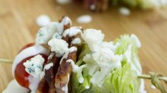 Lettuce wedges, bacon, and tomatoes are thread onto a bamboo toothpick and topped with blue cheese dressing for a fun wedge salad-on-a-stick appetizer.