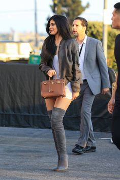 Kylie Jenner makes a statement in gray suede thigh-high boots, a dark green bomber jacket, and a tan mini Birkin bag in Los Angeles on Friday.